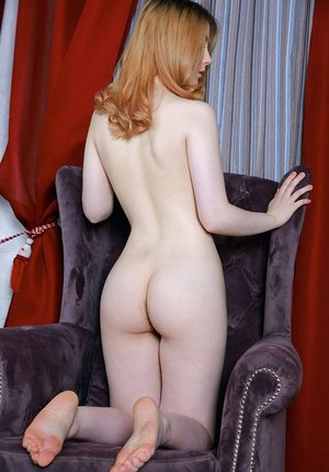 Natural redhead slips off her onesie to model nude on a velvet chair