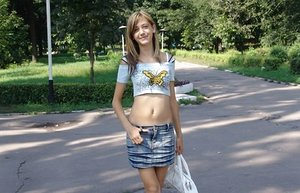 Thin teenage with long legs in short skirt looking sexy in public