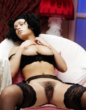 Busty Pammie Lee in black stockings spreading gams to rub her hairy pussy