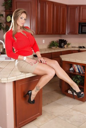 White cougar Eva Notty works free of a miniskirt for nude poses in kitchen