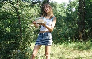 Lovely young girl in denim skirt undressing outdoors to smear food on her body