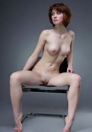 Naked lean Bretta A poses on a studio chair showcasing her petite perky tits
