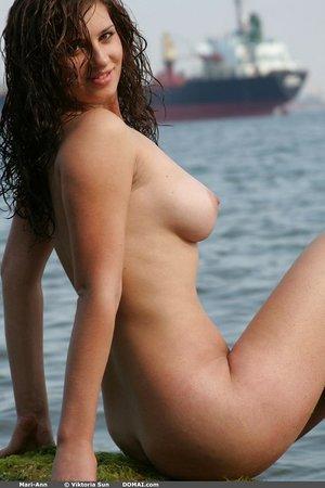 Fair skinned brunette chick Mari Ann flaunts her big naturals by the ocean