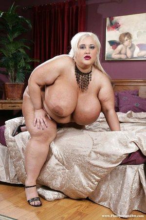Obese blonde woman slides a massager up her moist vagina