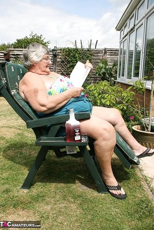 Naughty amateur granny Libby inserting a bottle in her fat pussy in the garden