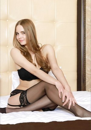 Splendid young brunette in black stockings & garter posing on her knees naked