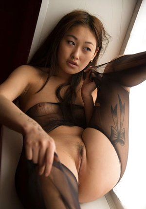 Asian solo girl Olga bares her lusty body and clean-shaved pussy near sunlit window