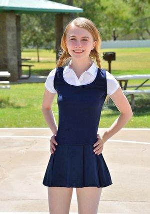 Tiny schoolgirl Sharlotte in uniform bends over for a naked upskirt outside