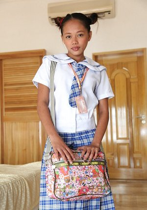 Young Asian schoolgirls lift their uniform skirts to show little bare pussy