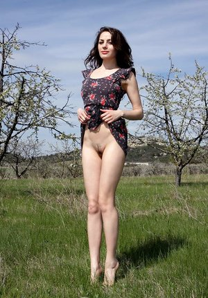 Brunette teenage Vani L hikes up skirt prior to pose nude in a field
