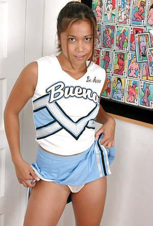 Asian babe opening up shaved teenage pussy after shedding cheerleader uniform